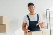 veselý pohyb v uniformě drží digitální tablet v blízkosti krabic v bytě