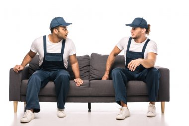 Full length of shocked multicultural movers looking at each other while sitting on sofa on white stock vector