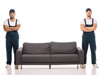 Full length of multicultural movers standing with crossed arms near couch on white stock vector
