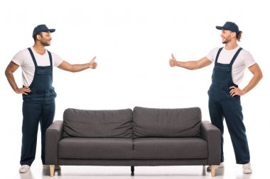 Full length of multicultural movers showing thumbs up and looking at each other near couch on white stock vector
