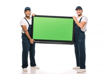 Full length of happy multicultural movers carrying plasma tv with green screen on white stock vector