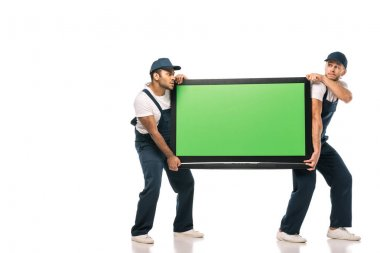Full length of multicultural movers stealing plasma tv with green screen on white stock vector