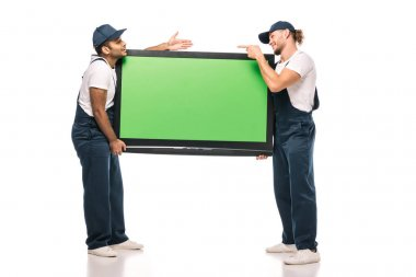 Full length of surprised multicultural movers pointing at each other while carrying plasma tv with green screen and on white stock vector