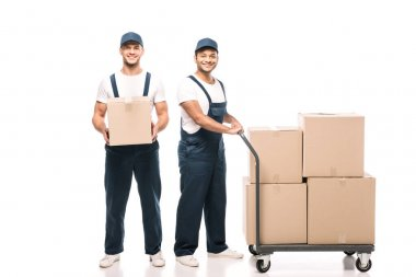Full length of happy multicultural movers in uniform and caps near hand truck with carton boxes on white stock vector