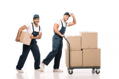 Full length of positive multicultural movers in uniform and caps walking near hand truck with carton boxes on white stock vector