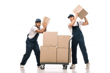 Full length of shocked multicultural movers in uniform holding carton boxes near hand truck with packages on white stock vector