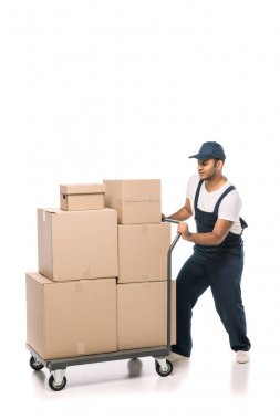 Full length of indian mover in overalls pulling heavy hand truck with carton boxes on white stock vector