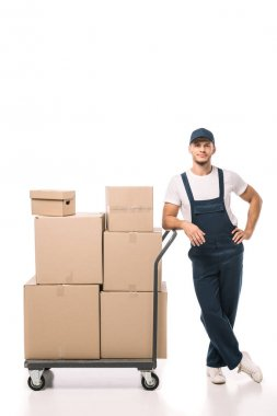 Full length of cheerful mover in uniform and cap leaning on hand truck with carton boxes on white stock vector