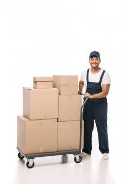 Full length of happy indian mover in overalls standing near hand truck with carton boxes on white stock vector