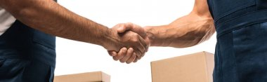 Cropped view of movers shaking hands near boxes isolated on white, banner stock vector