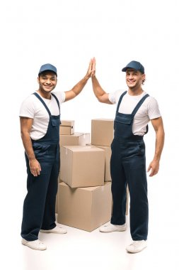 Full length of happy multicultural workers giving high five near boxes on white stock vector