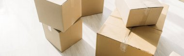 Stacked carton boxes on floor in modern apartment, banner stock vector