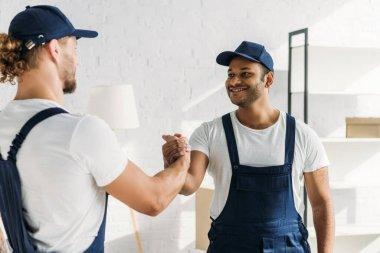 Happy multiethnic workers shaking hands in apartment stock vector