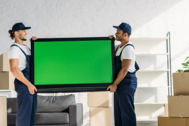 Side view of happy multicultural movers in uniform carrying plasma tv with green screen in apartment stock vector