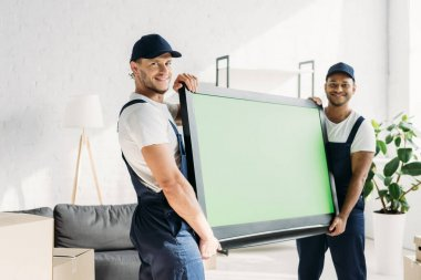 Happy multicultural movers in uniform carrying plasma tv with green screen in apartment stock vector
