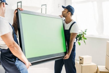 Multicultural movers in caps and uniform carrying plasma tv with green screen in apartment stock vector