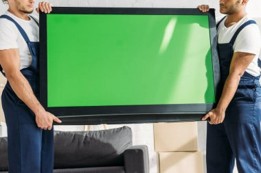 Cropped view of multicultural movers in uniform carrying plasma tv with green screen in apartment stock vector