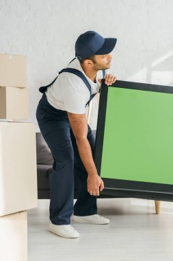 Indian mover in uniform carrying plasma tv with green screen in apartment stock vector