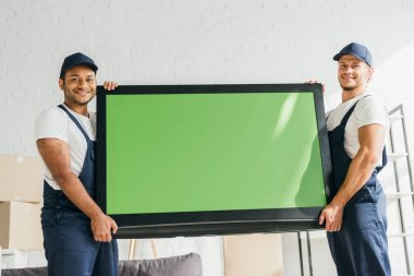 Smiling multicultural movers in uniform carrying plasma tv with green screen in apartment stock vector