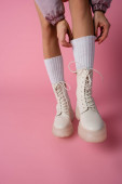 cropped view of female legs in boots and socks on pink background