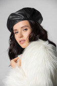 brunette young woman in stylish white faux fur jacket and leather beret posing on grey background