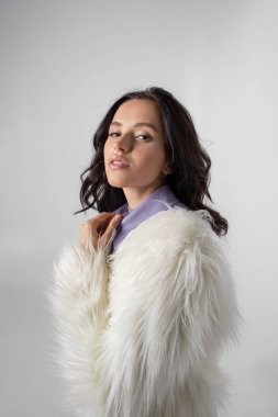 Brunette young woman in stylish white faux fur jacket posing on grey background stock vector