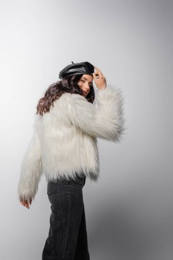 Brunette young woman in stylish white faux fur jacket and leather beret posing on grey background stock vector