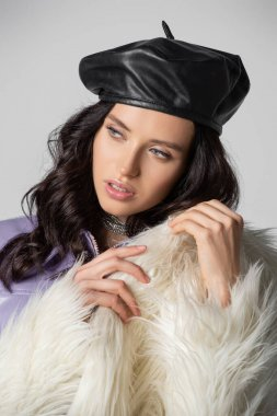 Elegant brunette young woman in stylish white faux fur jacket and leather beret posing on grey background stock vector