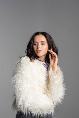 Elegant brunette young woman in stylish white faux fur jacket posing on grey background stock vector