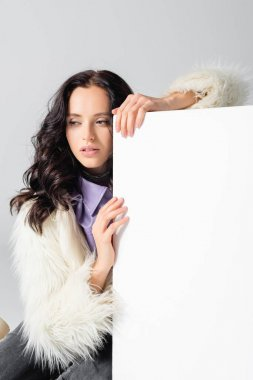 Elegant brunette young woman in faux fur jacket posing near cube on white background stock vector