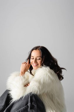 Smiling brunette young woman in faux fur jacket posing on white background stock vector