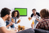 excited multiethnic football fans holding beer near lcd tv on wall on blurred foreground