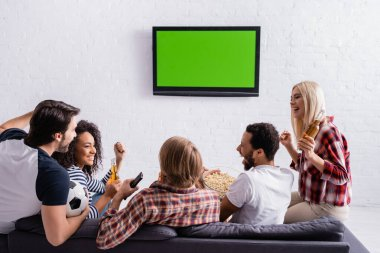 Happy multicultural football fans showing win gesture near led tv on wall stock vector