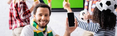 Cheerful african american man holding smartphone with blank screen near multiethnic football fans on blurred background, banner stock vector
