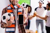 mosolygós férfi labdarúgó fan sál gazdaság labda és okostelefon üres képernyő közelében multikulturális barátok elmosódott háttér