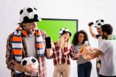 izgatott labdarúgó rajongó gazdaság foci labda és okostelefon üres képernyő közelében multietnikai barátok koccintás sör homályos háttér