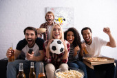 cheerful woman holding soccer ball while watching football competition with excited multiethnic friends