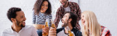cheerful multicultural friends holding bottles of beer during party, banner