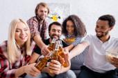 veselí multikulturní přátelé cinkání lahví piva na rozmazané popředí