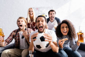 excited multiethnic football fans screaming while watching championship at home