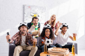 excited multicultural friends watching football championship and showing win gesture
