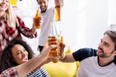 vzrušené multietnické přátelé cinkání lahví piva během párty, rozmazané pozadí