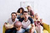 Geschockte multikulturelle Freunde mit geschminkten Gesichtern sehen Rugby-Meisterschaft zu Hause