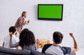 vzrušený muž křičí v blízkosti vedl TV, zatímco multietnické sportovní fanoušci ukazující vítězství gesto