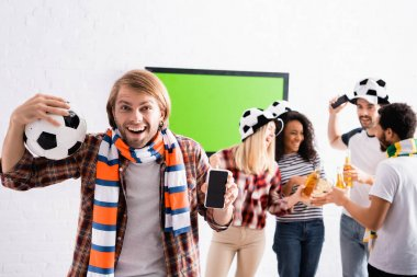 Excited man holding soccer ball and smartphone with blank screen near multiethnic friends on blurred background stock vector