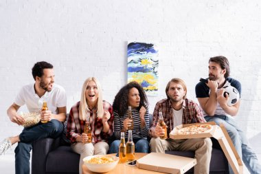 Worried and excited football fans watching championship with beer, pizza and chips at home stock vector