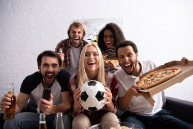 Excited multiethnic friends watching football championship with beer and pizza, blurred foreground stock vector