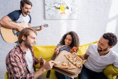 multicultural friends eating pizza on sofa while young man playing acoustic guitar