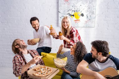 Young man playing acoustic guitar to excited multiethnic friends with beer, popcorn and pizza stock vector