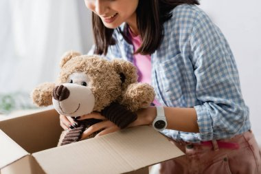 Cropped view of volunteer smiling while putting soft toy in box in charity office stock vector